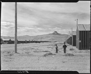 Heart Mountain Relocation Center, Heart Mountain, Wyoming. Looking west on F street, main thoroughfare of this relocation center, with its namesake Heart Mountain looming in the background. By Parker, Tom, Photographer (NARA record: 4682167) (U.S. National Archives and Records Administration) [Public domain], via Wikimedia Commons.