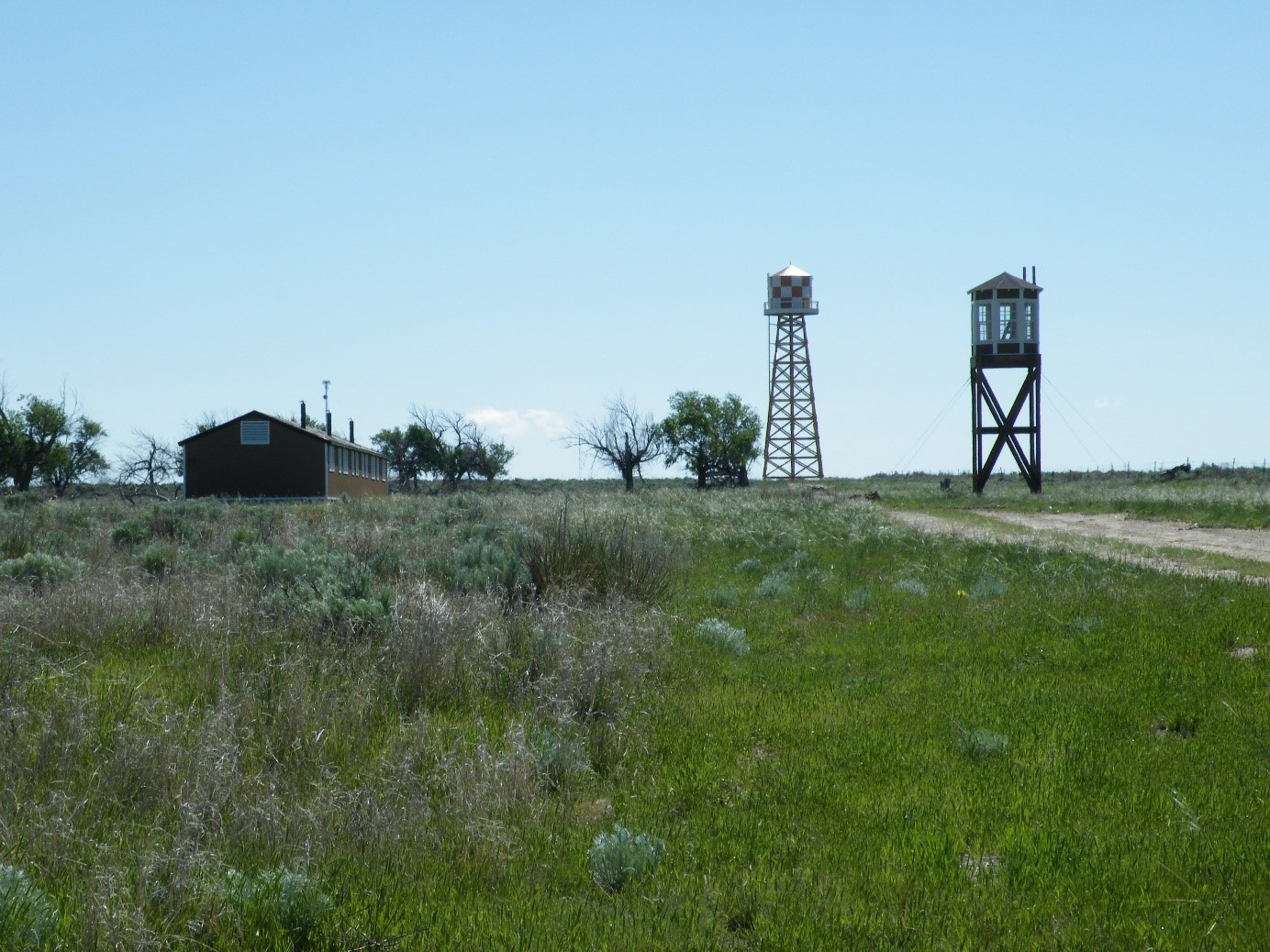 Restored barrack, water tower, and guard tower at Amache. Photo by Mitch Homma.