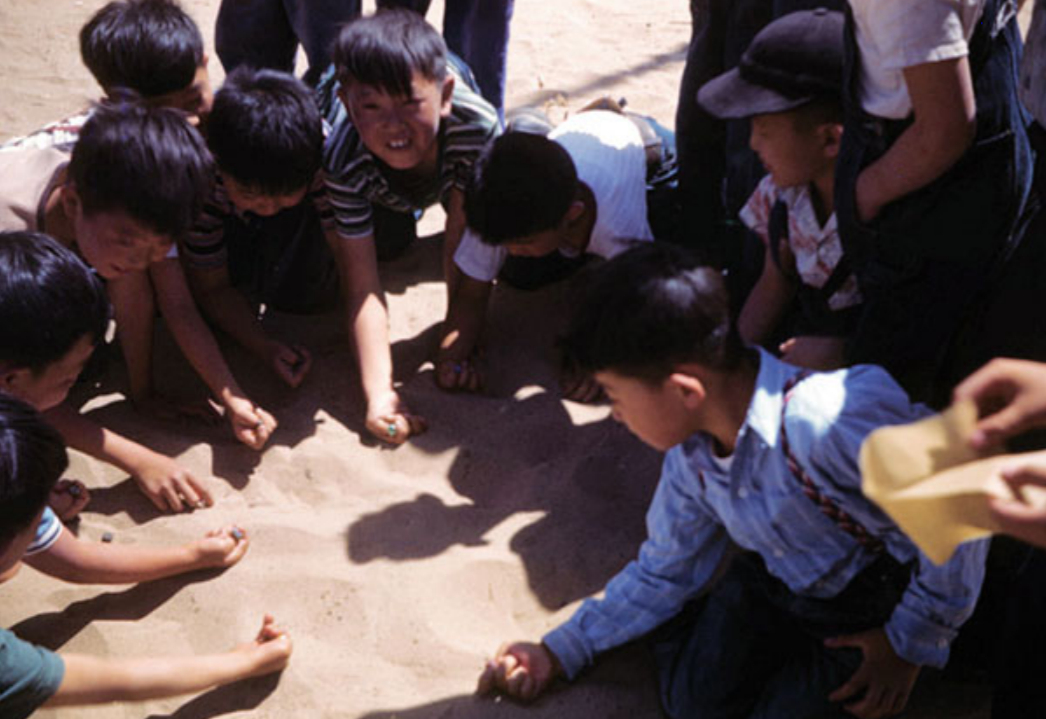 A group of young boys playing marbles in the sand at Amache. Photo courtesy the McClelland Collection held by the Amache Museum, Granada, Colorado.